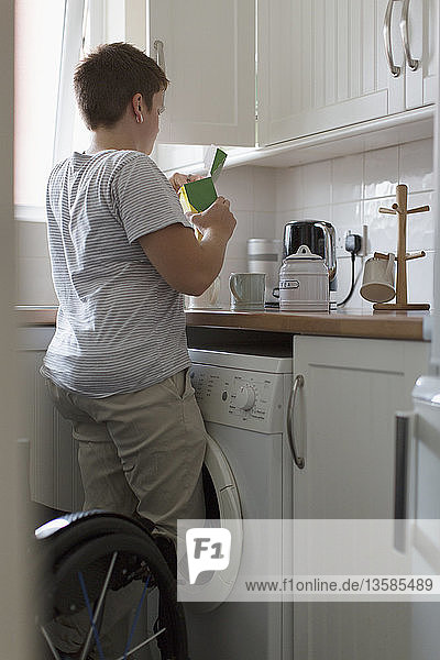 Young woman preparing tea in apartment kitchen