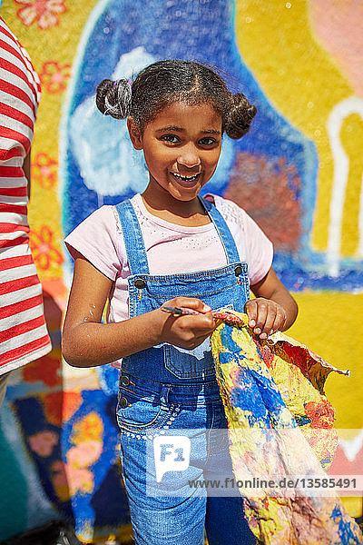 Portrait smiling girl painting vibrant mural on sunny wall