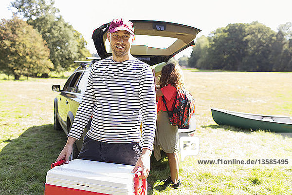 Portrait smiling man carrying camping cooler  unloading car in sunny field