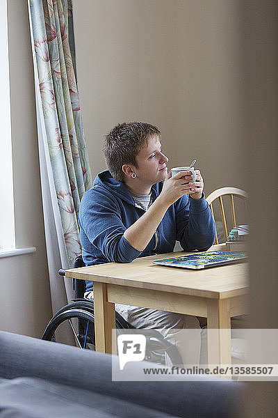 Thoughtful young woman in wheelchair drinking tea at dining table