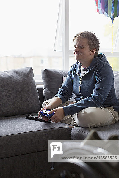Smiling young woman playing video game on sofa