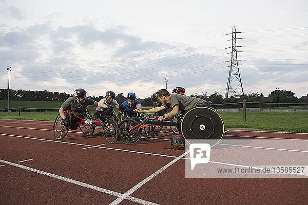 Paraplegic athletes huddling on sports track  training for wheelchair race