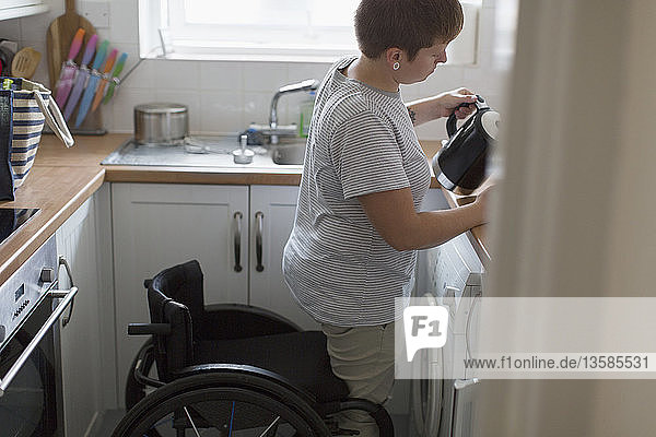 Young woman with wheelchair pouring tea in apartment kitchen