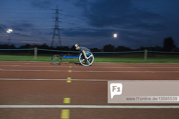 Young female paraplegic athlete speeding along sports track in wheelchair race at night