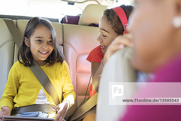 Happy sisters riding in back seat of car with digital tablet