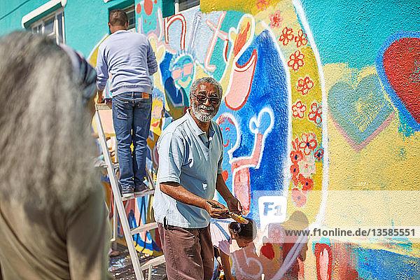 Senior man volunteer painting vibrant mural on sunny wall