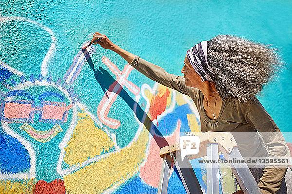 Senior woman painting vibrant mural on sunny wall