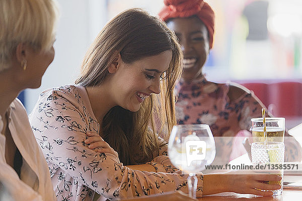 Young women friends laughing  drinking cocktails in bar