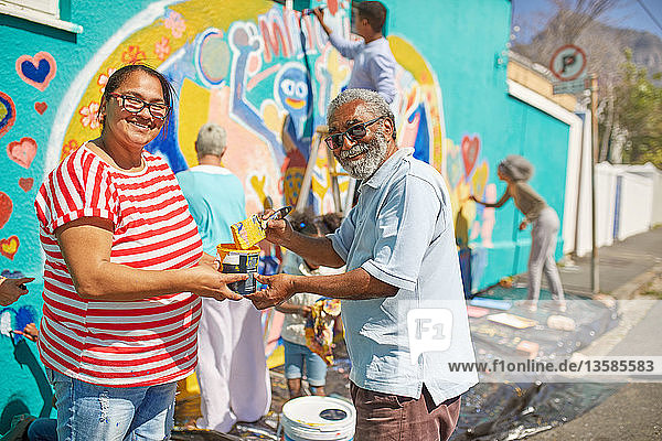Portrait happy community volunteers painting mural on sunny urban wall