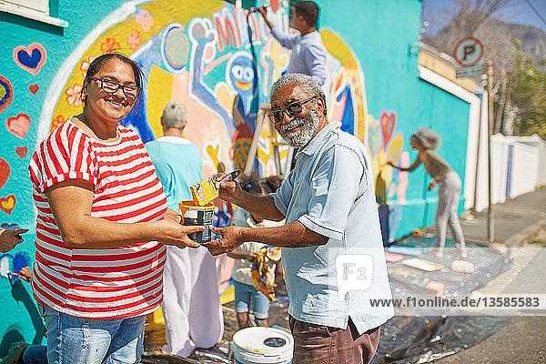 Portrait happy community volunteers painting mural on sunny urban wall