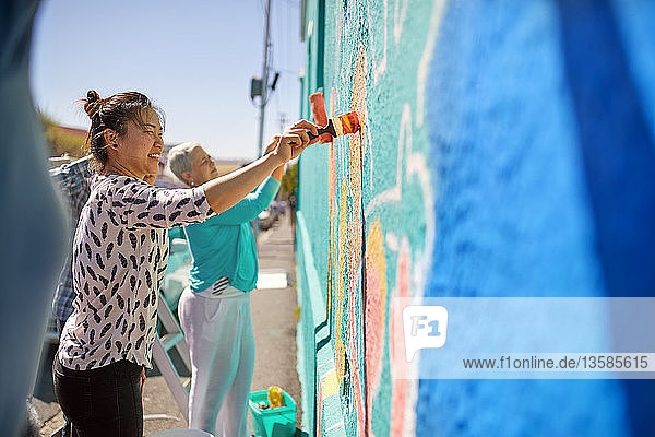 Women painting vibrant mural on sunny urban wall