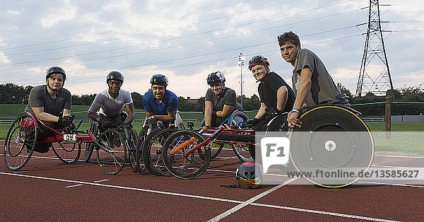 Portrait confident paraplegic athletes training for wheelchair race on sports track