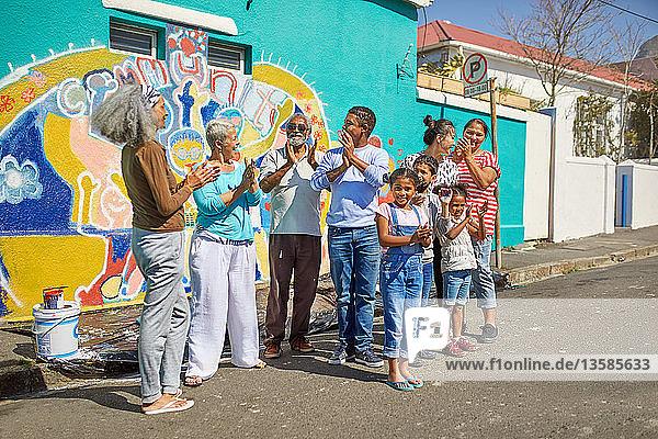 Happy community volunteers celebrating painted mural on sunny urban wall