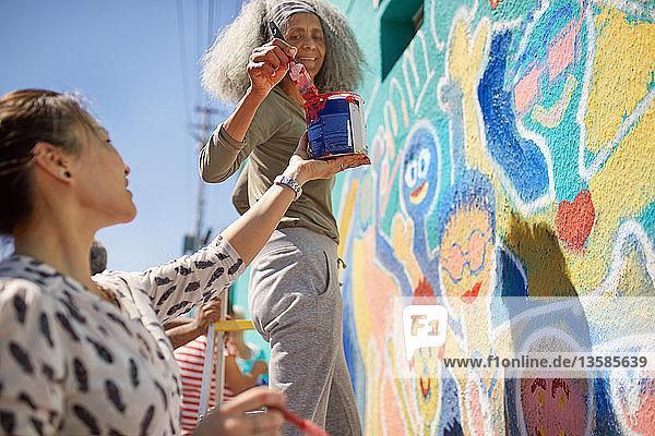 Female volunteers painting vibrant community mural on sunny urban wall