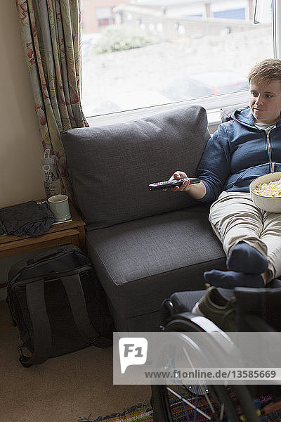 Young woman watching TV with feet up on wheelchair