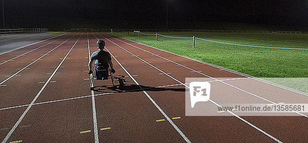 Paraplegic athlete training for wheelchair race on sports track at night