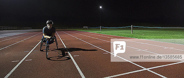 Portrait confident  determined young female paraplegic athlete training for wheelchair race on sports track at night