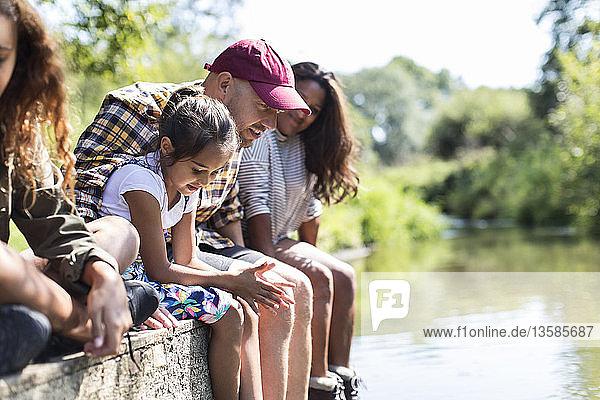 Familie sitzt am Rande des Flussufers