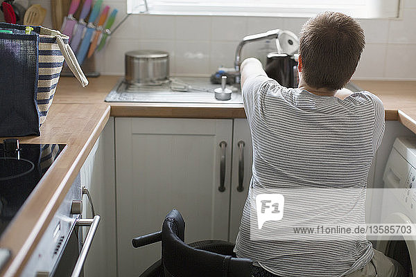 Young woman in wheelchair filling kettle for tea at apartment kitchen sink