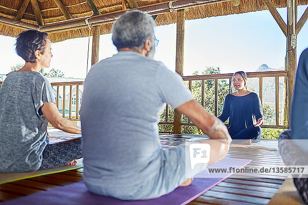 Female yoga instructor leading class in hut during yoga retreat