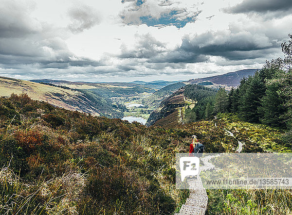 Woman hiking along idyllic mountain path with scenic landscape view  Wicklow NP  Ireland