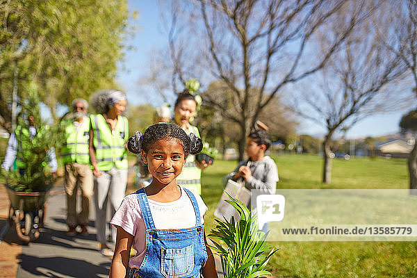 Portrait smiling  confident girl volunteering  planting trees in sunny park