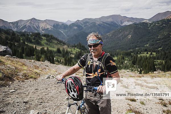 Portrait active senior man mountain biking in remote landscape  Chilcotin Mountains  British Columbia  Canada