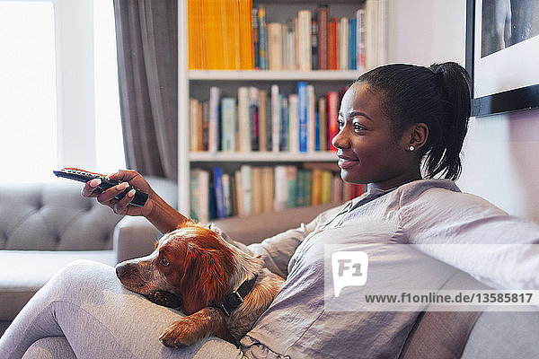 Young woman and dog relaxing  watching TV on living room sofa