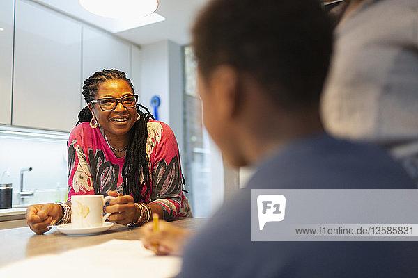 Smiling grandmother talking to grandson in kitchen