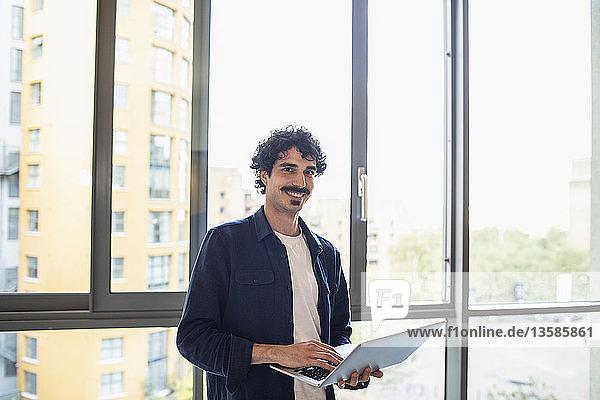 Porträt eines selbstbewussten Mannes  der einen Laptop am Fenster einer städtischen Wohnung benutzt