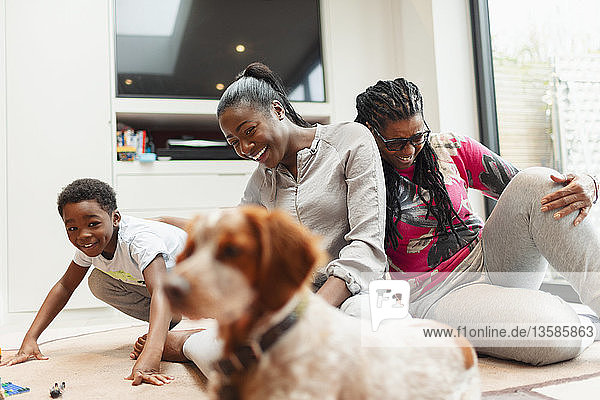 Multi-generation family playing with dog in living room