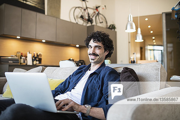 Portrait smiling man using laptop on apartment sofa