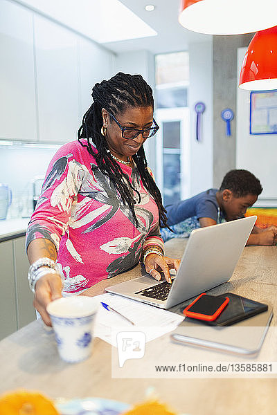 Mature woman using laptop in kitchen