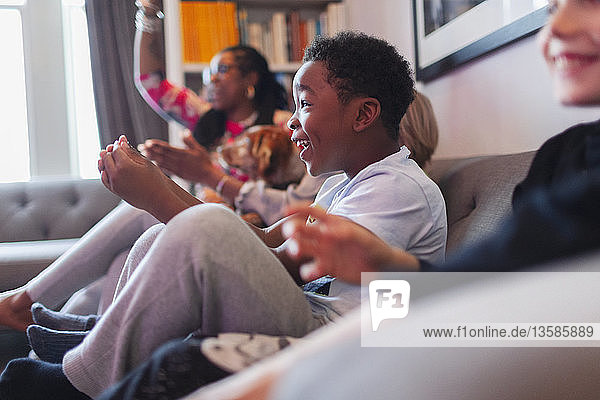 Enthusiastic boy playing video game with family on living room sofa