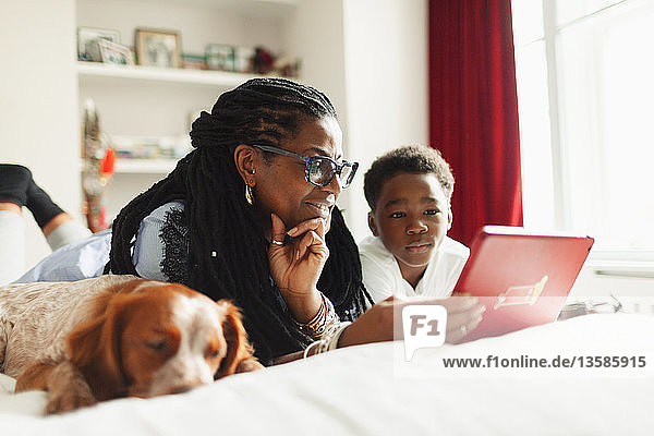 Grandmother and grandson using digital tablet next to sleeping dog on bed
