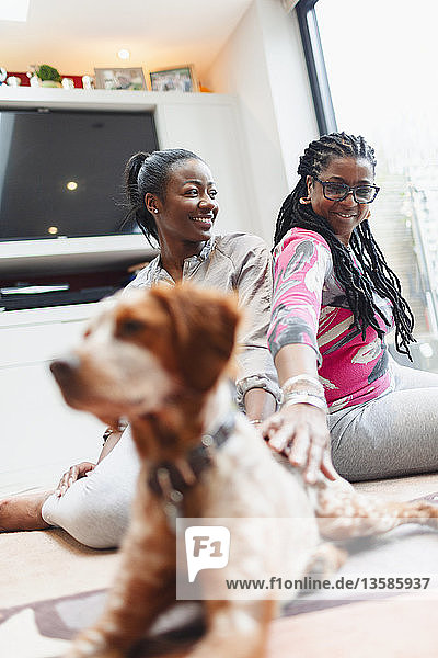Mother and adult daughter with dog on living room floor