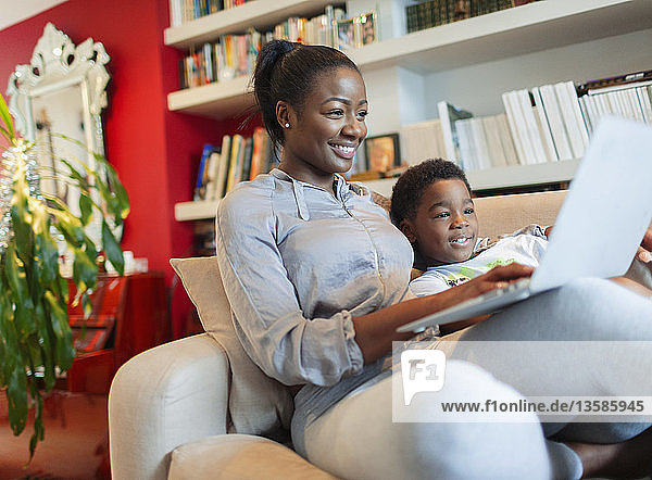 Mother and son using laptop on living room sofa