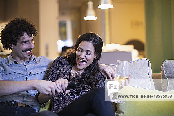 Playful couple fighting over the remote control  watching TV and drinking white wine on sofa