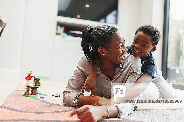 Affectionate mother and son on living room floor
