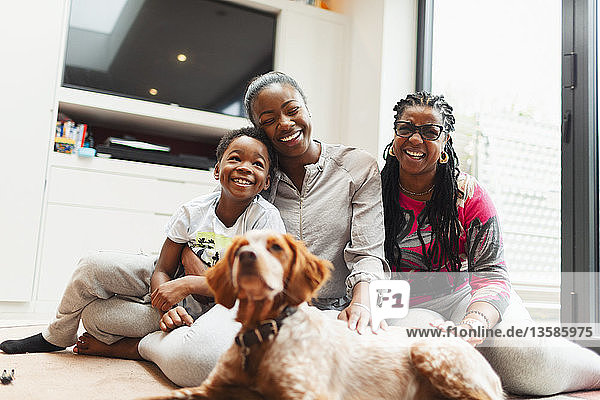 Portrait happy multi-generation family with dog on living room floor