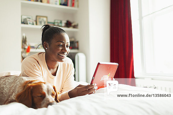 Smiling young woman using digital tablet next to sleeping dog on bed