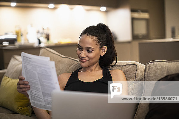 Smiling woman reading paperwork and using laptop on sofa