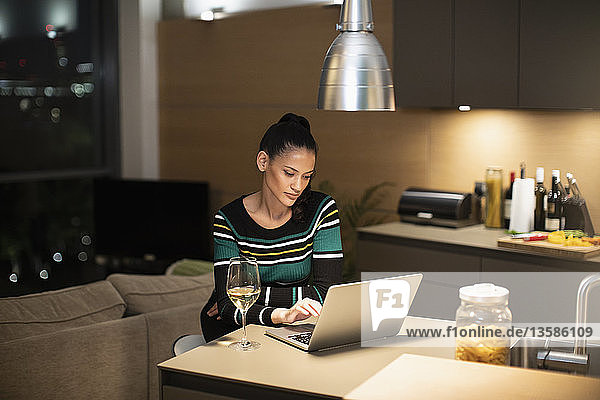 Focused woman using laptop and drinking white wine in apartment kitchen at night