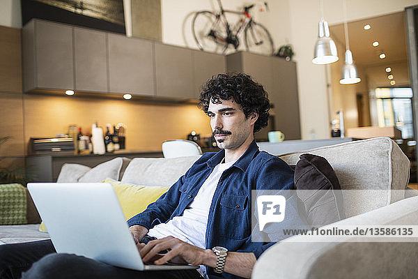Man using laptop on living room sofa