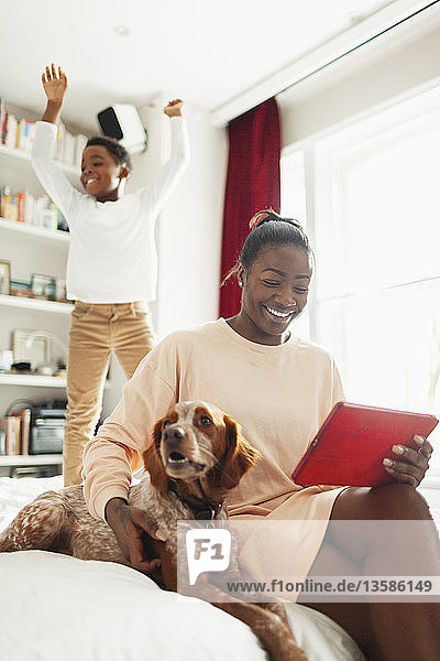 Playful boy jumping on bed behind dog and mother with digital tablet
