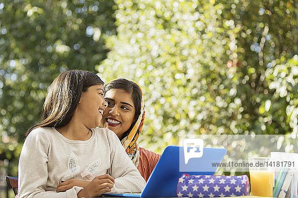 Glückliche Mutter und Tochter mit Laptop auf der Terrasse