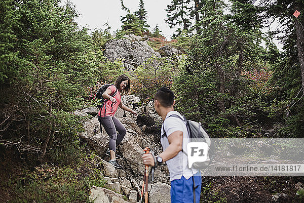 Couple hiking down rocks in woods