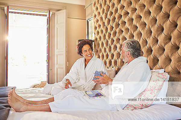 Mature couple in bathrobes on hotel bed