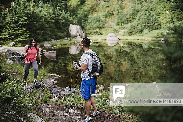 Couple hiking along lake in woods