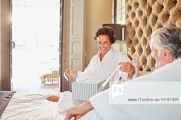 Husband watching happy wife opening gift on hotel bed